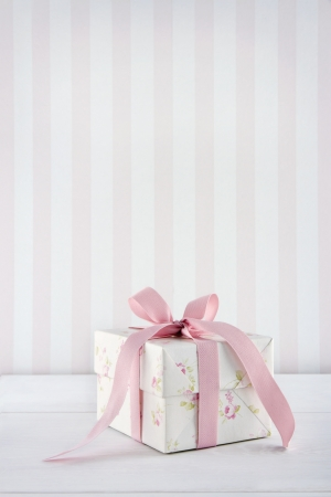 Floral pattern gift box tied with pink ribbon on white wooden background with copy space Stock Photo