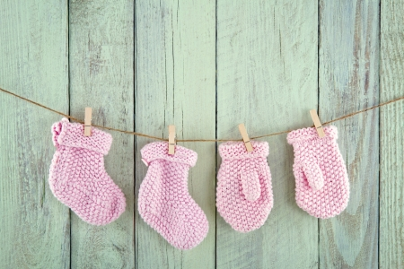 Pink baby girl socks and mittens on vintage clothesline on green vintage wooden background