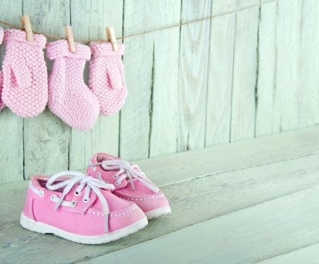 Pink toddler shoes on wooden light green vintage background with copy space
