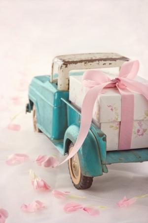 Alte antike Spielzeug LKW mit einem Geschenk-Box mit rosa Schleife auf romantische Spitze Hintergrund und Blütenblättern Standard-Bild - 19264343