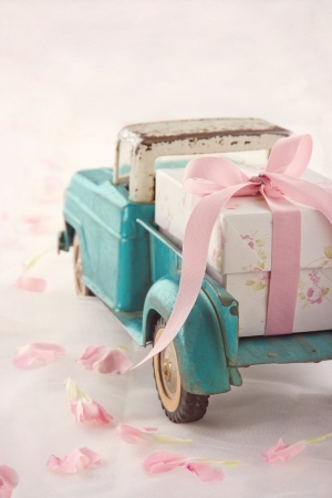 Old antique toy truck carrying a gift box with pink ribbon on romantic lace background and flower petals Banco de Imagens