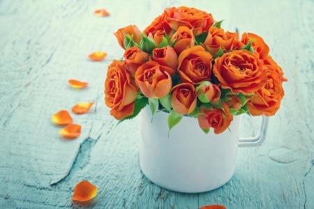 rosas naranjas: Vintage rosas naranjas editados en una taza blanca sobre azul shabby fondo de madera elegante