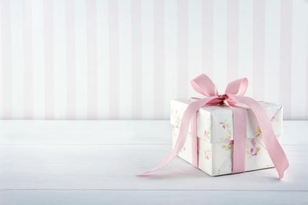 Bloemmotief gift box gebonden met roze lint op witte houten achtergrond met kopie ruimte