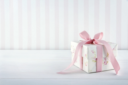 gift giving: Floral pattern gift box tied with pink ribbon on white wooden background with copy space Stock Photo