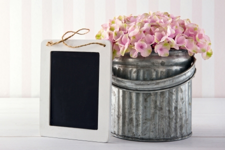 Pink hydrangea flowers in a metal vase on vintage background with empty blackboard for copy space Stock Photo