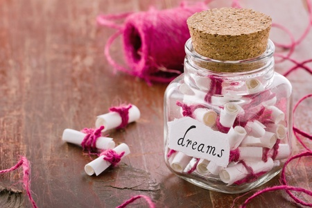 optimism: Dreams written on a white rolled paper in a glass jar on rustic vintage wooden background, dreaming optimism concept