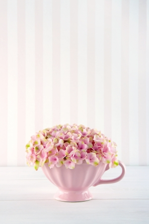 Pink hydrangea flowers in a shabby chic mug on pastel vintage background with copy space Stock Photo