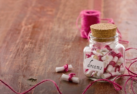 optimism: Dreams written on a white rolled paper in a glass jar on rustic vintage wooden background with copy space, dreaming optimism concept