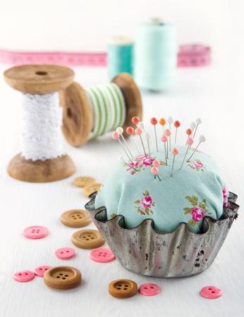 Grüne handgemachte Blumen Nadelkissen in eine alte Metall-Cupcake mit Tasten und Garnrollen und Spitzen, Nähen Konzept Hintergrund Standard-Bild - 19541461