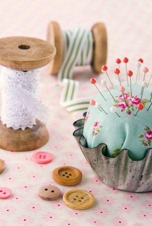Green handmade floral pincushion in an old metal cupcake with buttons and spools of thread and lace, sewing concept background photo
