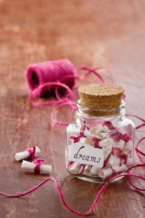 rolled paper: Dreams written on a white rolled paper in a glass jar on rustic vintage wooden background, dreaming optimism concept