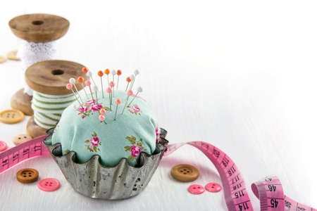 Green handmade floral pincushion in an old metal cupcake with buttons and spools of thread and lace, sewing concept background