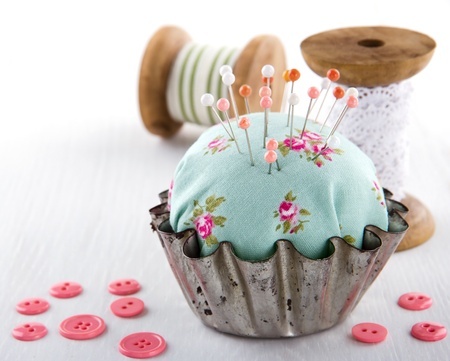 old spools: Green handmade floral pincushion in an old metal cupcake with buttons and spools of thread and lace, sewing concept background