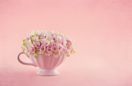 mother s day: Pink hydrangea flowers in a shabby chic mug on pastel vintage background with copy space Stock Photo
