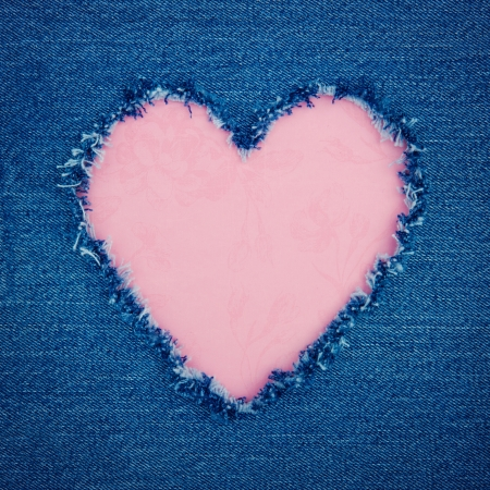 jeans fabric: Pink vintage heart shape for copy space torn from blue denim jeans fabric, romantic love concept background