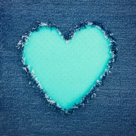 Blue vintage heart shape for copy space torn from denim jeans fabric, romantic love concept background Stock fotó
