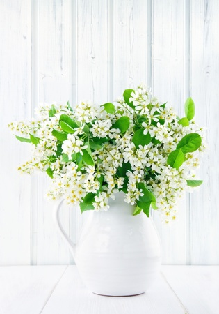 Bouquet of white bird cherry branches in a ceramic jug on vintage wooden table