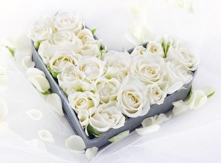 꽃 꽃잎 꿈꾸는 레이스 배경에 오래 된 빈티지 금속 심장 모양의 트레이에 하얀 웨딩 장미 스톡 콘텐츠