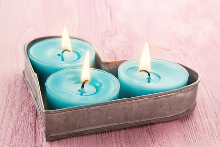 Blue burning candles on a heart shaped tray with romantic pink vintage wooden background with blurred boked photo