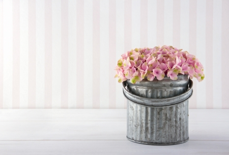 Pink hydrangea flowers in a metal bucket on vintage striped background with copy space