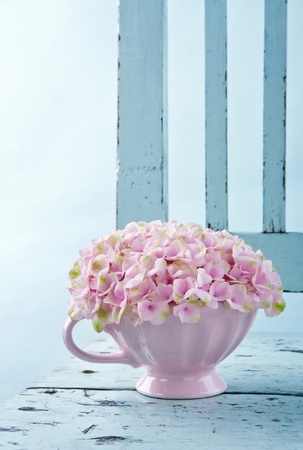 Cup full of pink hydrangea flowers on blue old shabby chic vintage chair Stockfoto