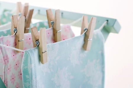 Closeup of pastel color laundry drying on vintage wooden drying rack with copy space