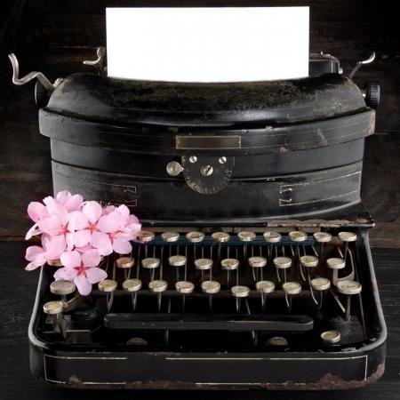 로맨틱 한 핑크색 벚꽃 꽃과 복사본 공간에 대 한 오래 된 골동품 검은 빈티지 타자기와 빈 종이,