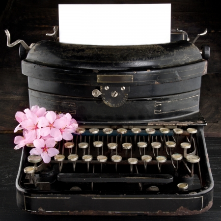 Old antique black vintage typewriter and empty paper for copy space, with pink romantic cherry blossom flowers