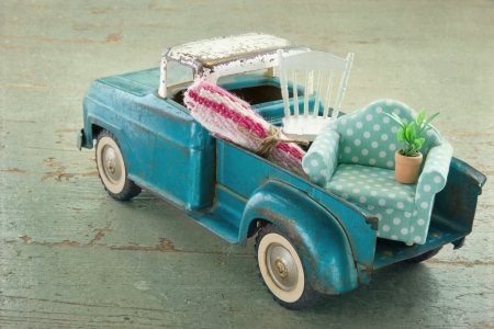 vintage furniture: Old vintage toy truck packed with furniture - moving houses concept