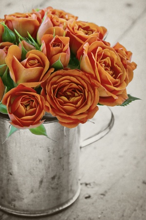 antique vase: Vintage bouquet of orange roses on black and white rustic textured background Stock Photo