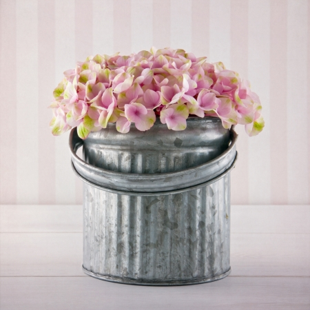 Pink hydrangea flowers in a metal bucket on vintage striped background