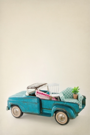 Old vintage toy truck packed with furniture - moving houses concept and copy space