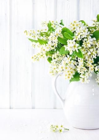 빈티지 나무 테이블에 세라믹 용기에 흰색 조류 벚꽃 분기의 꽃다발