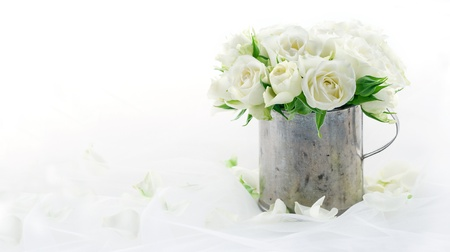 Bouquet of white wedding roses in an old vintage metal cup on dreamy lace background with floral petals Stock Photo