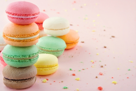 Pile of colorful macaroons on pastel pink background with small crumbs photo