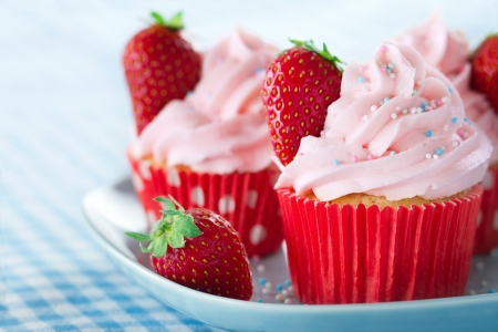 Pink cupcakes with fresh strawberries and sprinkles on a vintage tray and blue retro towel Standard-Bild