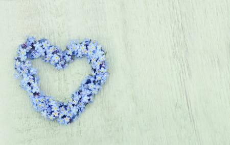 Heart shaped flower wreath of forget-me-not on green wooden background