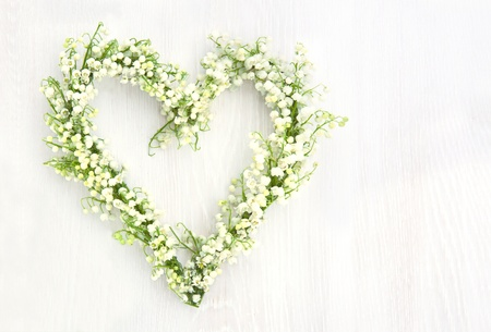 Heart shaped flower wreath of lilys of valley on white wooden background