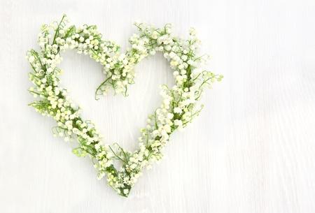 hart bloem: Hartvormige bloemen krans van lilys van de vallei op witte houten achtergrond Stockfoto