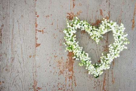 Heart shaped flower wreath of lilys of the valley on green wooden background
