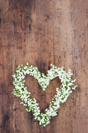 Heart shaped flower wreath of lilys of the valley on rustic wooden background