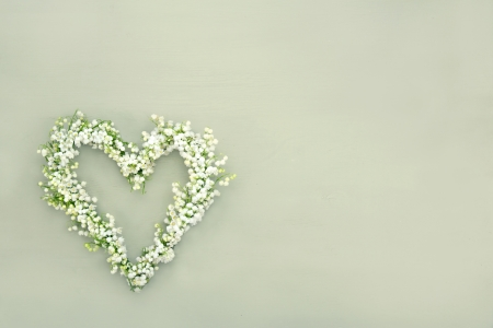 Heart shaped flower wreath of lilys of valley on green wooden background Stockfoto