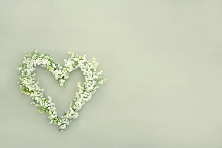 Heart shaped flower wreath of lilys of valley on green wooden background Standard-Bild