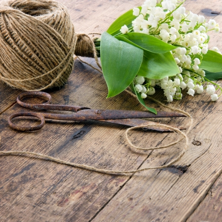 antique scissors: Bouquet of spring flowers lilys of the valley with old rusty antique scissors and ball of brown twine Stock Photo
