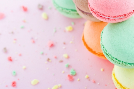 Pile of colorful macaroons on pastel pink background with small crumbs