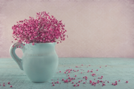 Pink dried babys breath flowers in a blue jug on wooden background and vintage wallpaper Stock Photo