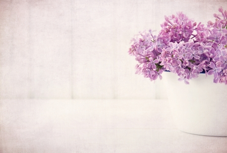 White vase with a bouquet of purple lilac spring flowers on vintage textured background photo