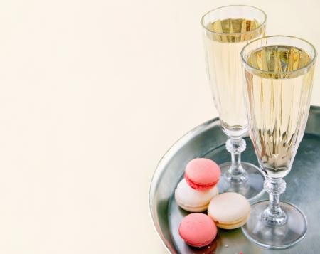 スパーク リング ワインまたは小さなカラフルなマカロンを銀のトレイにシャンパンを 2 杯