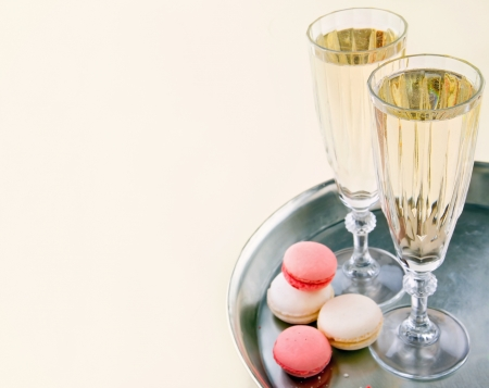 Two glasses of sparkling wine or champagne on a silver tray with small colorful macaroons 版權商用圖片