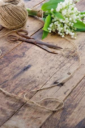 antique scissors: Bouquet di fiori primaverili lilys della valle con le vecchie forbici antiche arrugginite e palla di spago marrone